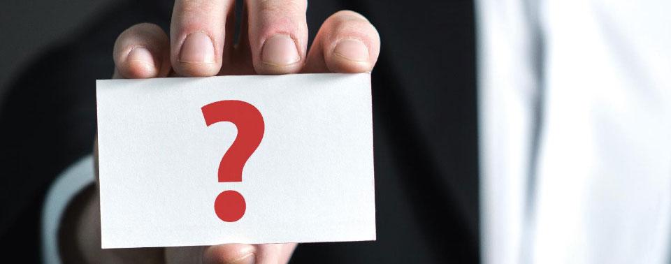 ręka trzymająca karteczkę ze znakiem zapytania