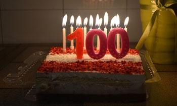 prostokątny tort ze świeczkami; na pierwszym planie świeczki w kształcie liczby 100